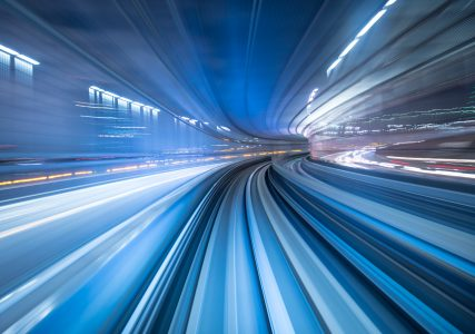 An long exposure photo of a train moving through an underground tunnel
